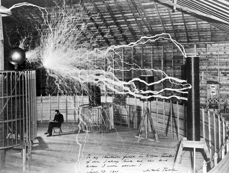 Nikola Tesla in zijn laboratorium in Colorado Springs (1899) naast zijn zogeheten magnifying transmitter, die een spanning van miljoenen volt opwekt. Tesla gebruikt de trucfoto ter promotie van zijn plan voor de wereldwijde, draadloze distributie van elektriciteit.